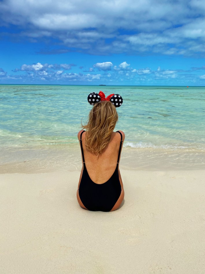 Tanya Foster sitting on the beach in a black one piece swimsuit and minnie mouse ears