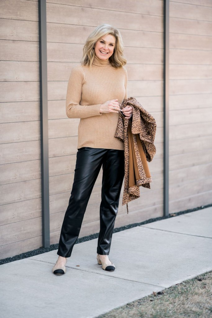 tanya foster in chico's camel ribbed turtleneck faux leather slim pants holding leopord print faux-suede trench coat