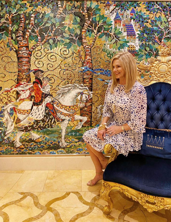 Tanya Foster sitting on a chair by a mural on a disney cruise in an eliza j dress