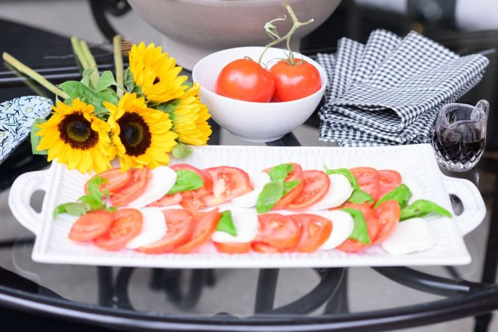 fresh caprese salad with tomato basil and mozzarella on vietri serving platter