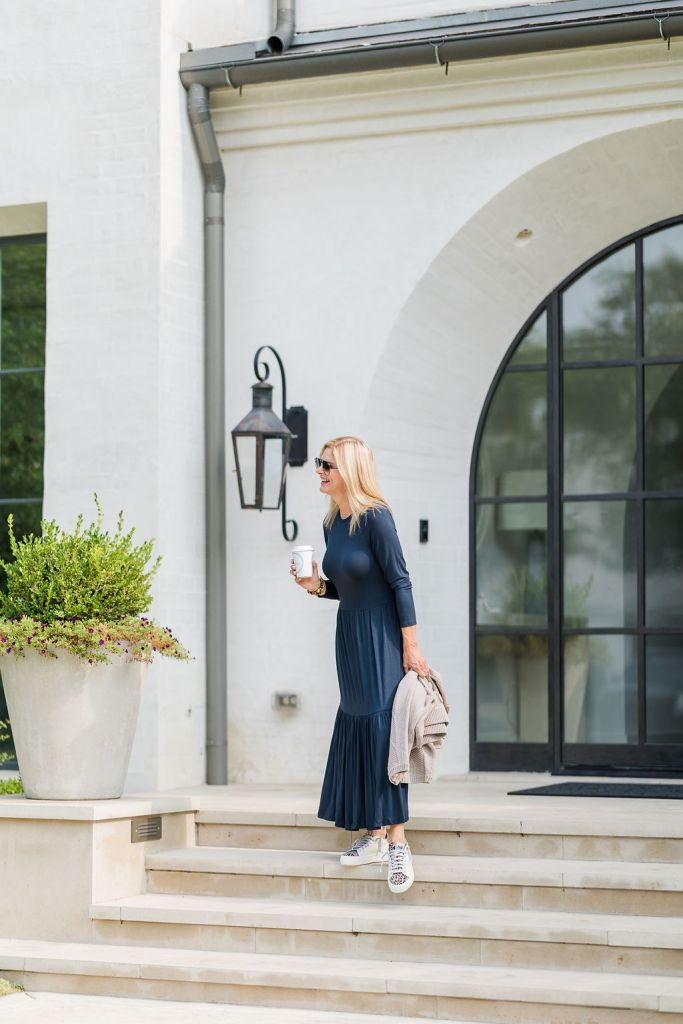 Tanya Foster wearing saint + sofia navy dress holding coffee and a sweater