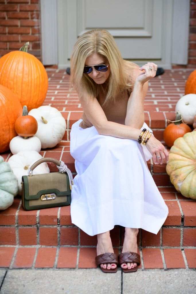 Tanya foster wearing STAUD dress with marc jacobs bag. and vince camuto slide sandals