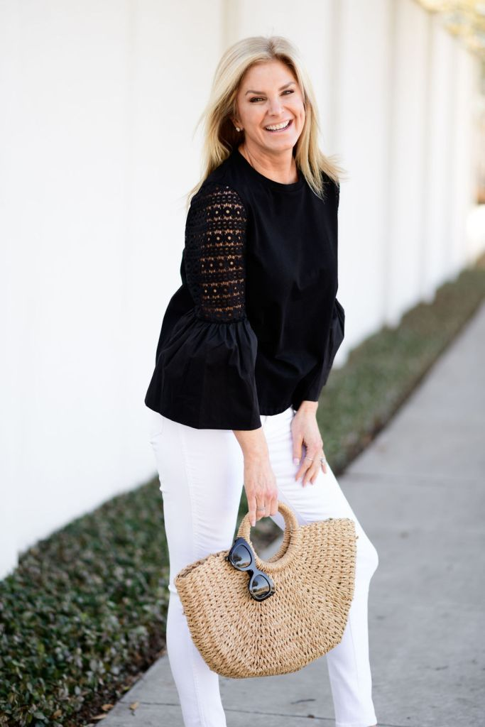 tanya foster wearing loft white jeans and black top with animal print jillie flats and straw bag