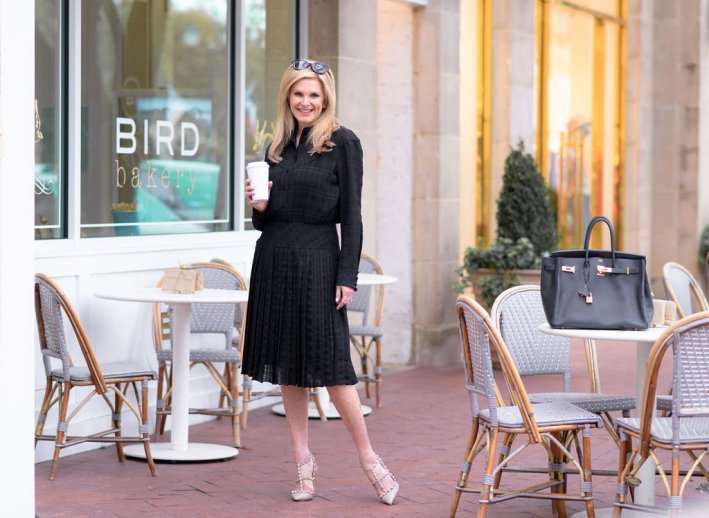 Tanya Foster holding a coffee in a Coach spring 2020 collection dress, Valentino heels and coach sunglasses