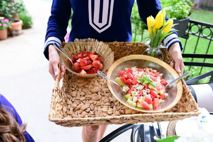 Tanya Foster holding a wicker tray of fruit in vietri bowls