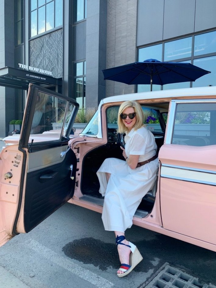 Tanya Foster visits Boston and shares her recommendations | Destination: Boston, Massachusetts Travel Guide by popular Dallas travel blogger, Tanya Foster: image of a woman wearing a white dress and sitting in a vintage car.