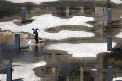 A man power washes the cement where Hudson's used to stand May 11, 2015. (Tanya Moutzalias | MLive Detroit)