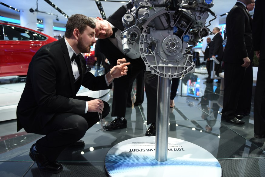 (left) Corey and Gus Ploss, of Clarkston, inspect an engine at the Ford display at the auto show's Charity Preview Friday evening, Jan. 15, 2016. Over 13,000Êattended the 2016 North American International Auto Show's 40th annual Charity Preview at Cobo Center in Detroit. Attendees, dressed in their very best for the black-tie event known as 'Auto Show Prom,' mingled on the showroom floor getting a look at the more than 750 vehicles before Saturday's public opening. (Tanya Moutzalias | MLive Detroit)
