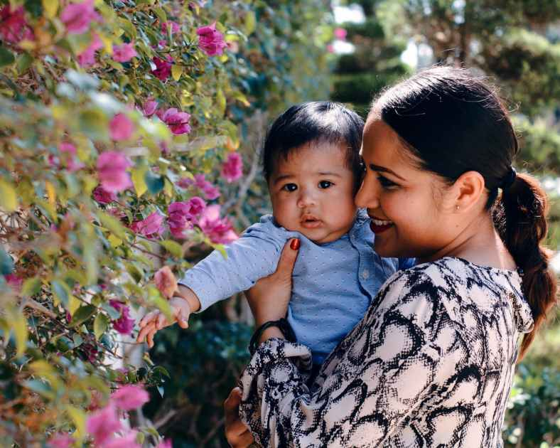 happy ethnic mother and baby enjoying sunny day in garden