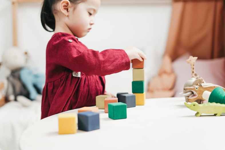 girl in red dress playing blocks