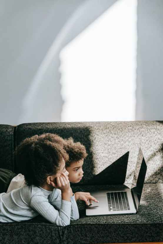 black children using touchpad of laptop on sofa