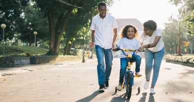man standing beside his wife teaching their child how to ride bicycle