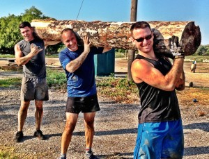 Jesse James Retherford, Monte, and Jonah carrying a giant log. The Art of Fitness Austin Texas.
