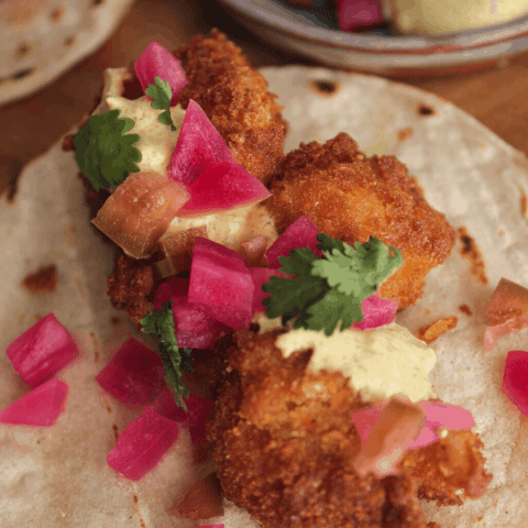 Close up of curried cauliflower taco with tortillas and tray of toppings in background.