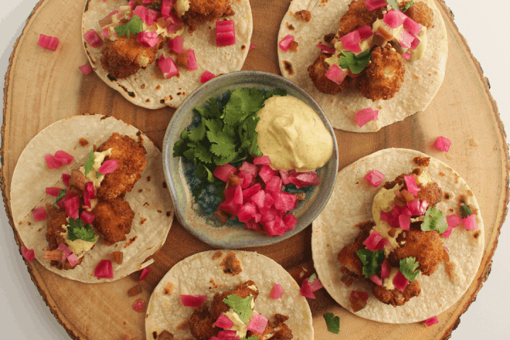 Five curried cauliflower tacos on a wood platter with bowl of toppings in middle.