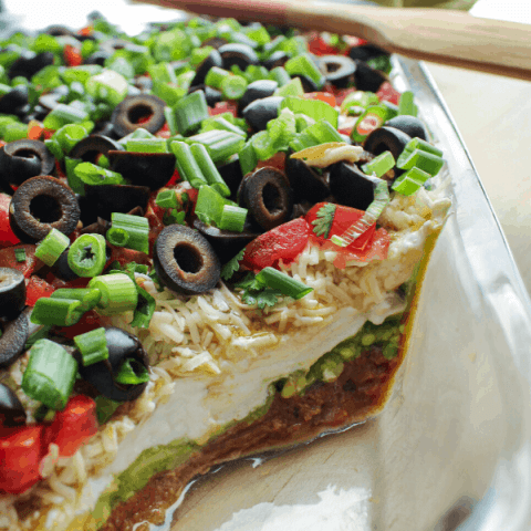 7 layer dip in glass bakin dish with wood spatula an basket of chips in background