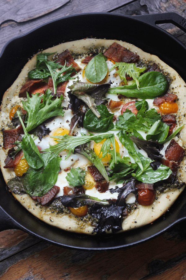 Breakfast BLT pizza cooked in cast-iron skillet made with everything bagel seasoning, pesto, fresh mozzarella, tomatoes, bacon, eggs, and fresh greens.