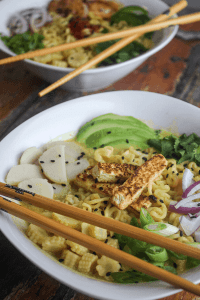 two bowls of ramen curry with veggies and chopsticks layed across top in white bowls on wood surface