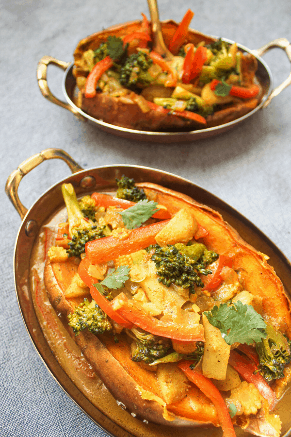 two stuffed sweet potatoes with vegetable coconut curry in copper dishes on blue surface