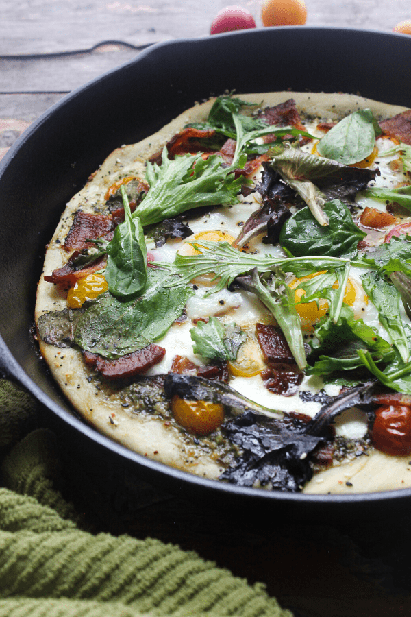 This breakfast BLT cast-iron pizza starts with a homemade dough sprinkled with everything bagel seasoning, is slathered in pesto, and topped with fresh mozzarella, tomatoes, bacon, eggs, and fresh greens.