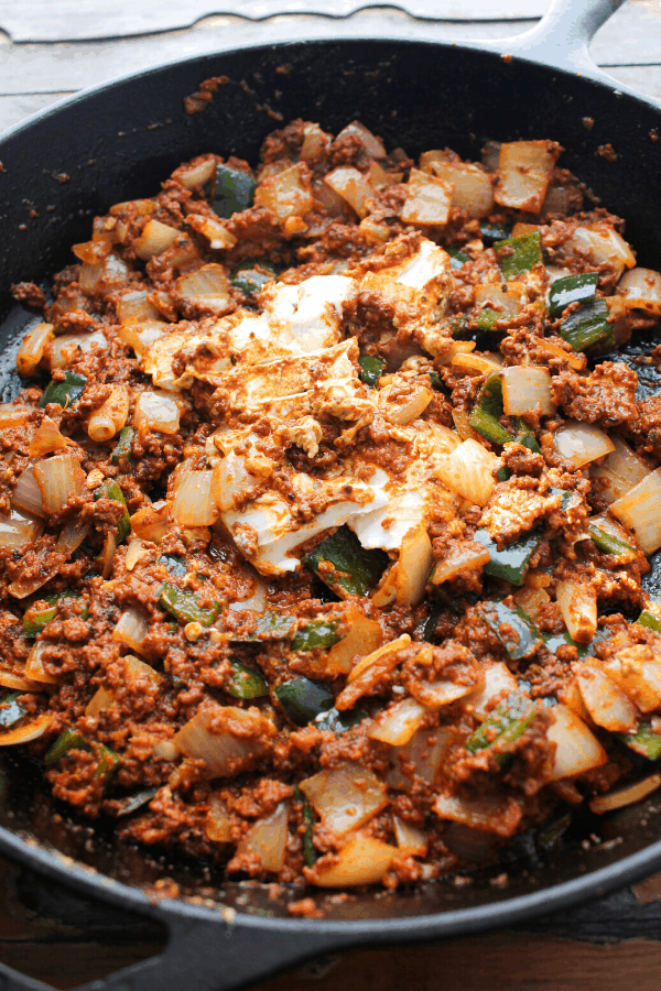 chorizo, diced white onion and poblano peppers and goat cheese in a cast iron skillet.