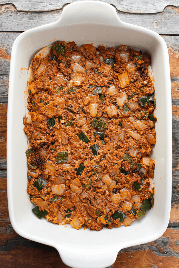 Chorizo, onion, poblano pepper, and goat cheese mixture spread out in white baking dish from above.