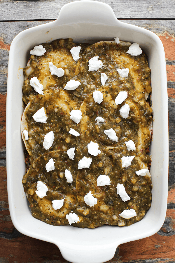 corn torillas covered in salsa verde and crumble goat cheese in white baking dish from above