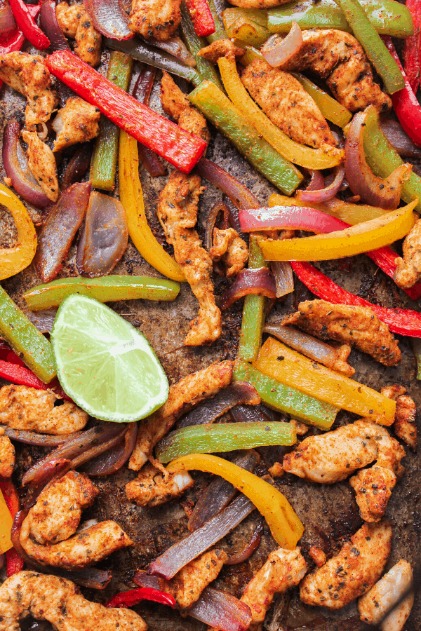 chicken fajita filling on sheet pan with lime wedge