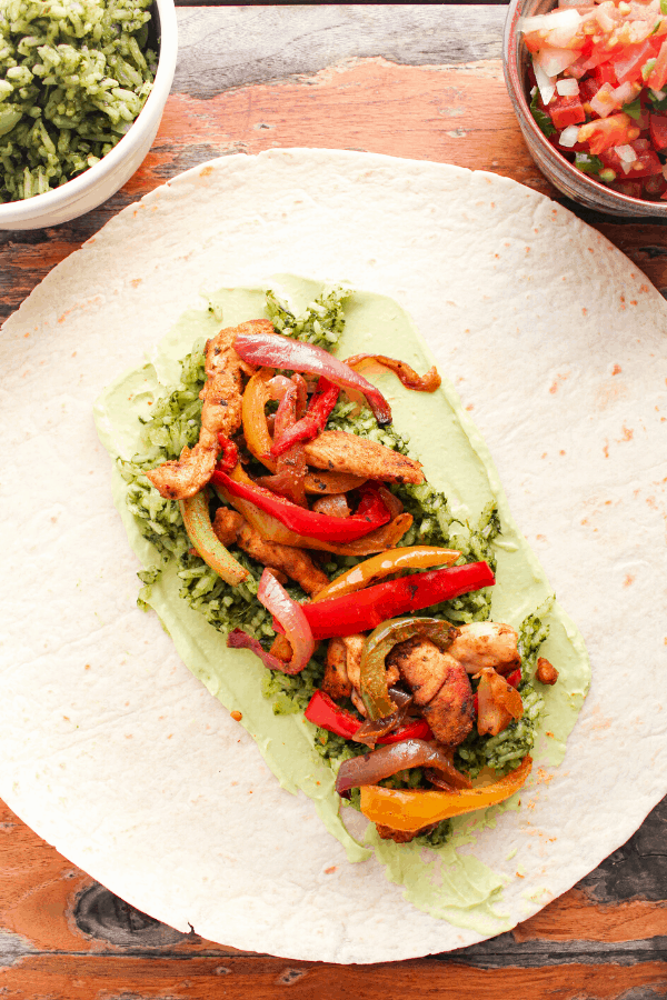flat tortilla layered with chicken fajita wrap ingredients on table with small bowl of green rice and pico de gallo.