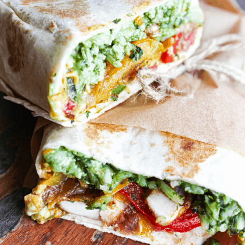 two halves of chicken fajita wraps stacked atop each other on wooden surface