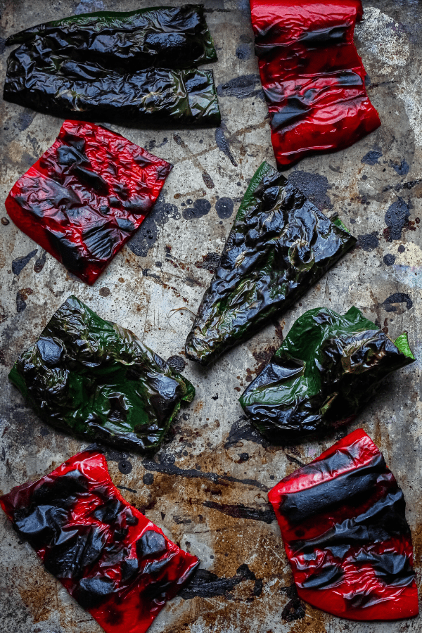roasted poblano and red bell peppers on a baking sheet shot from above