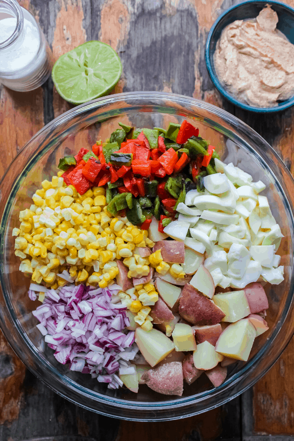 vegetables and eggs for potato salad in a large bowl with a jar of salt, lime slice, and small bowl of potato salad sauce on side shot from above