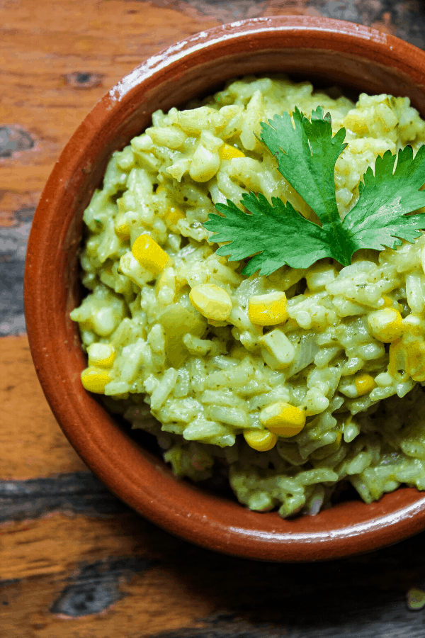 small bowl of creamy poblano rice w/ corn with sprig of cilantro shot from above