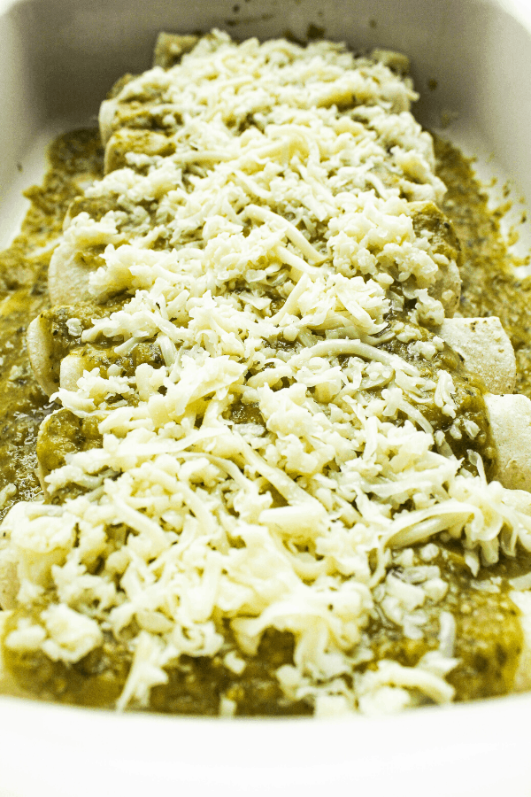 enchiladas covered with sauce and cheese in baking dish prior to cooking