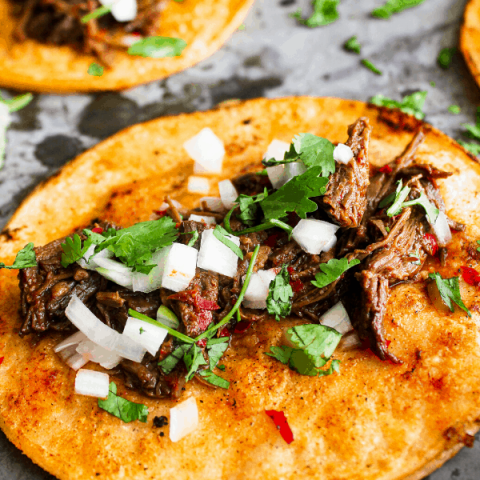 close up of beef birria taco with a second taco, lime wedge, and cilantro in the background