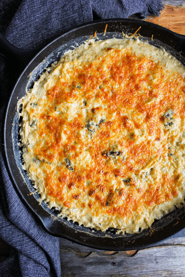 Full baked spinach artichoke casserole in cast-iron skillet shot from above.