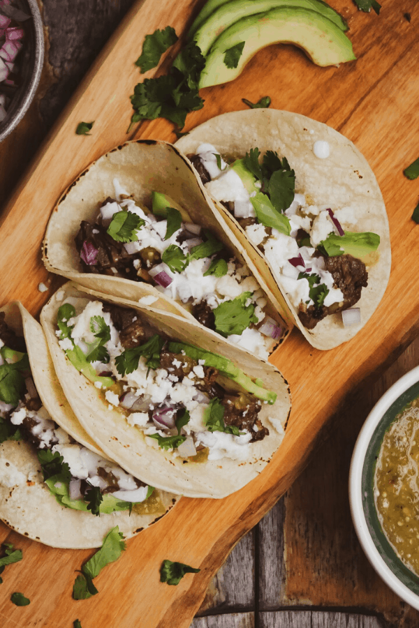 Four carne asada tacos with roasted pineapple habanero salsa on a wood cutting board with bowl of salsa on side.