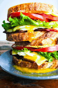 Two bacon, egg, & cheese sandwiches with lemon dill aioli stacked atop each other.