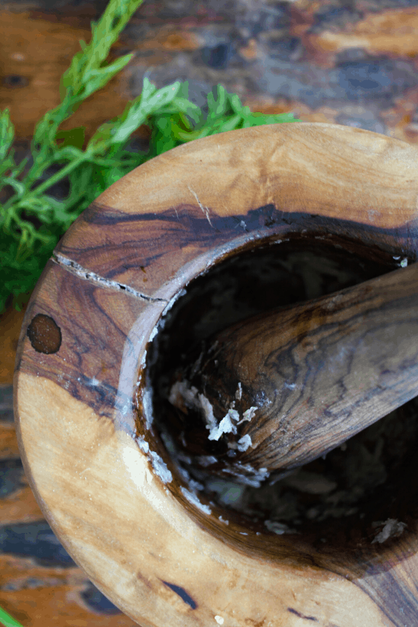 Wooden mortar and pestle with crushed garlic and salt with sprigs of dill in background.