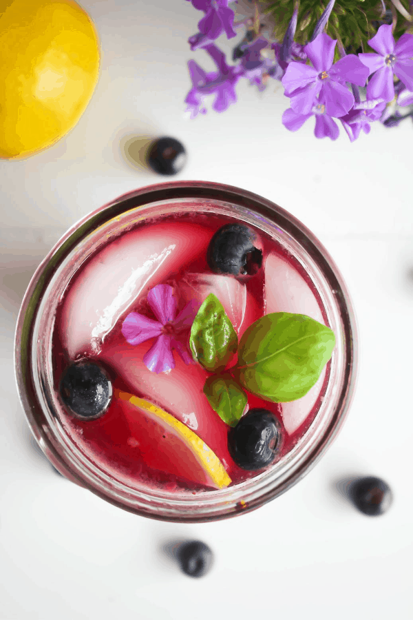 Top down shot of jar of blueberry basil lemonade garnished with lemon slice, blueberries, basil, and a single purple flower on a white surface with scattered blueberries, a lemon, and purple flowers.