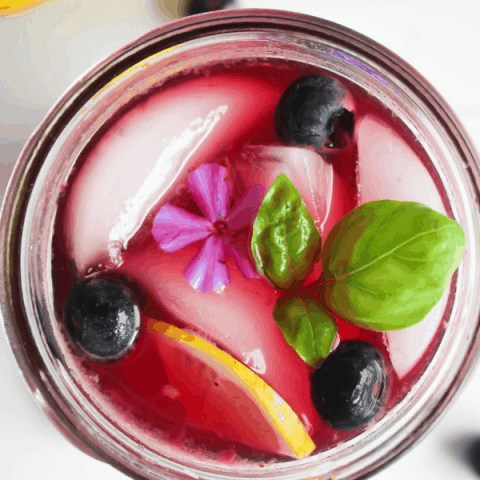 Close-up top down shot of blueberry basil lemonade garnished with blueberries, basil, lemon slice, and a single purple flower.