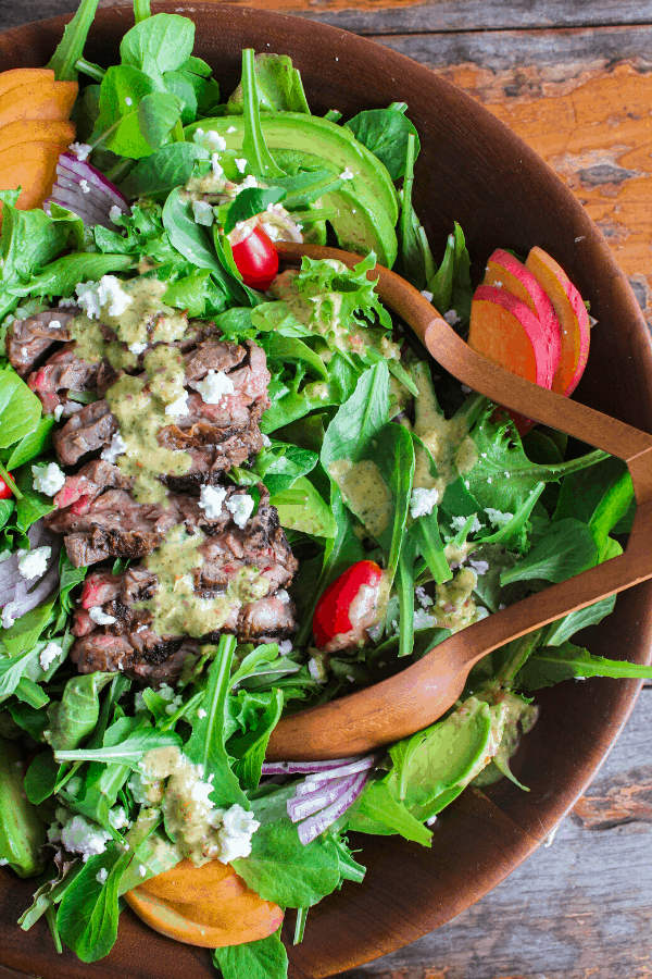 Shot of half of bowl of grilled Steak Salad w/ Habanero Peach Vinaigrette with salad tongs shot from above.