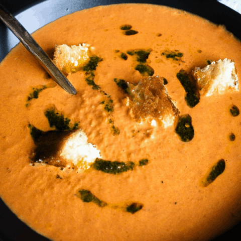 Bowl of tomato soup with spoon with second bowl of soup in background.