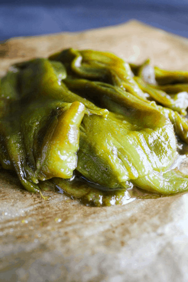Close-up shot of roasted, peeled, and deseeded chiles on a piece of parchment paper.