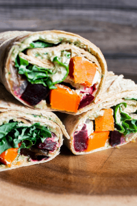 Three halves of autumn harvest vegetable wraps stacked atop one another.