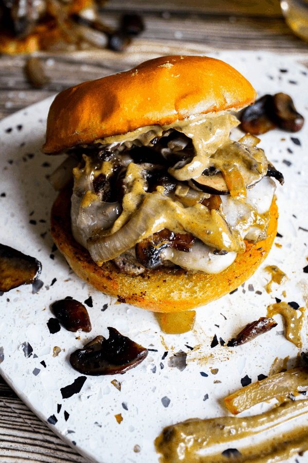 Platter topped with mushroom & Swiss burger with top bun sliding off.