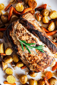 Close up top down shot of apple cider brined pork loin with roasted veggies.