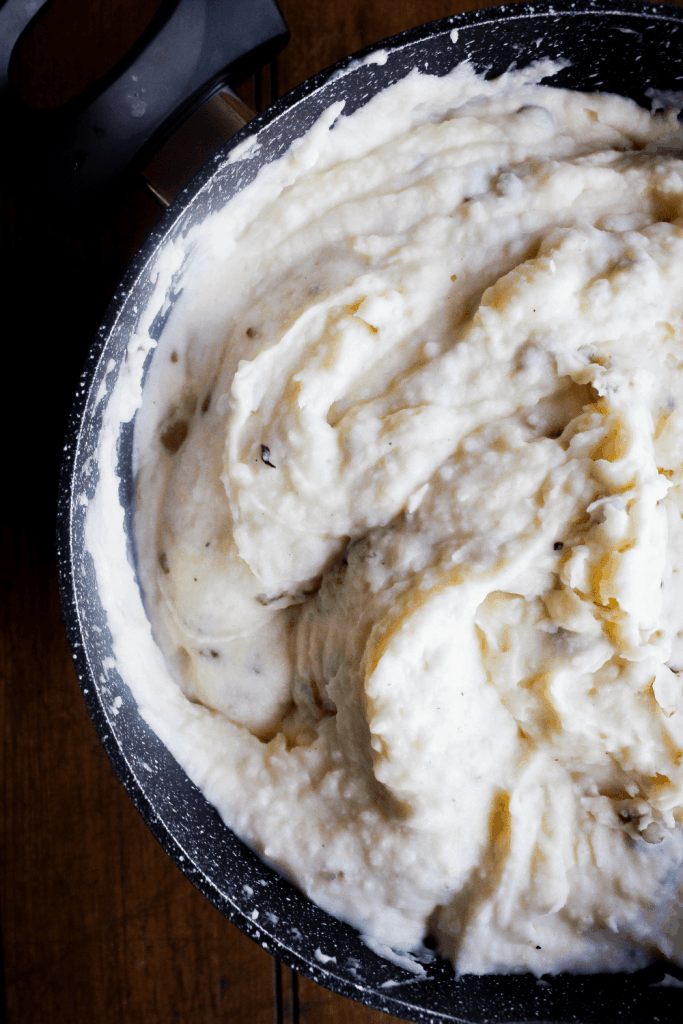 Top down shot of finished mashed potatoes in a pot.