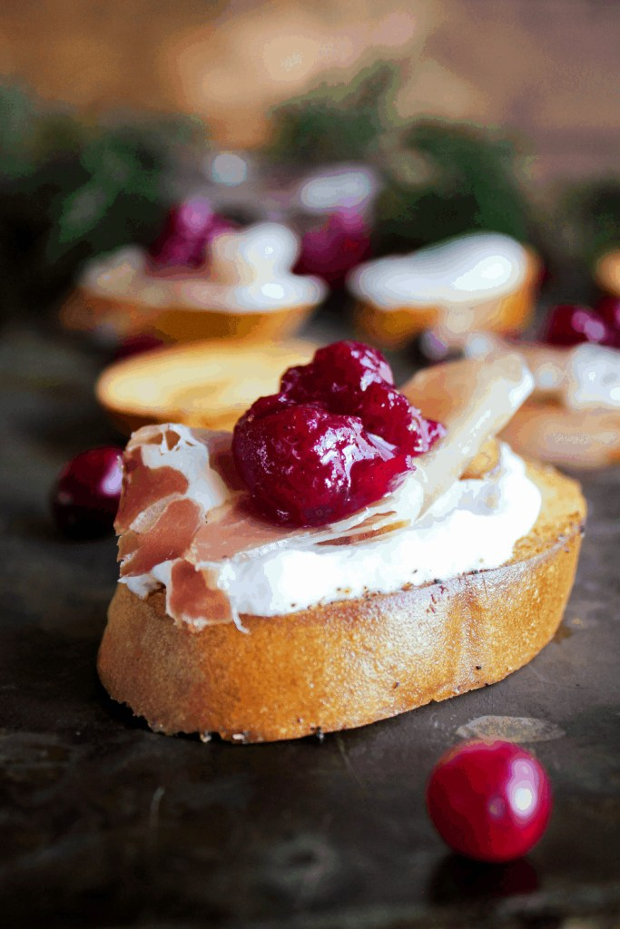 Whipped goat cheese crostini with prosciutto and cranberry sauce with additional crostini in background.