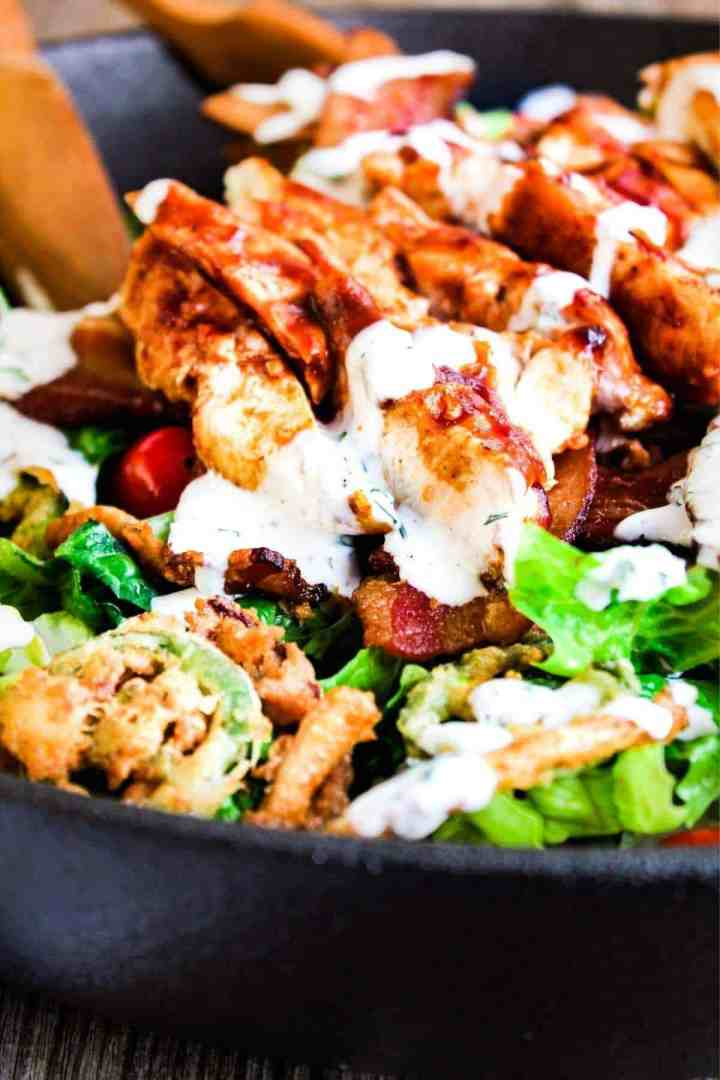 Close up of bbq chicken bacon ranch salad with tongs.